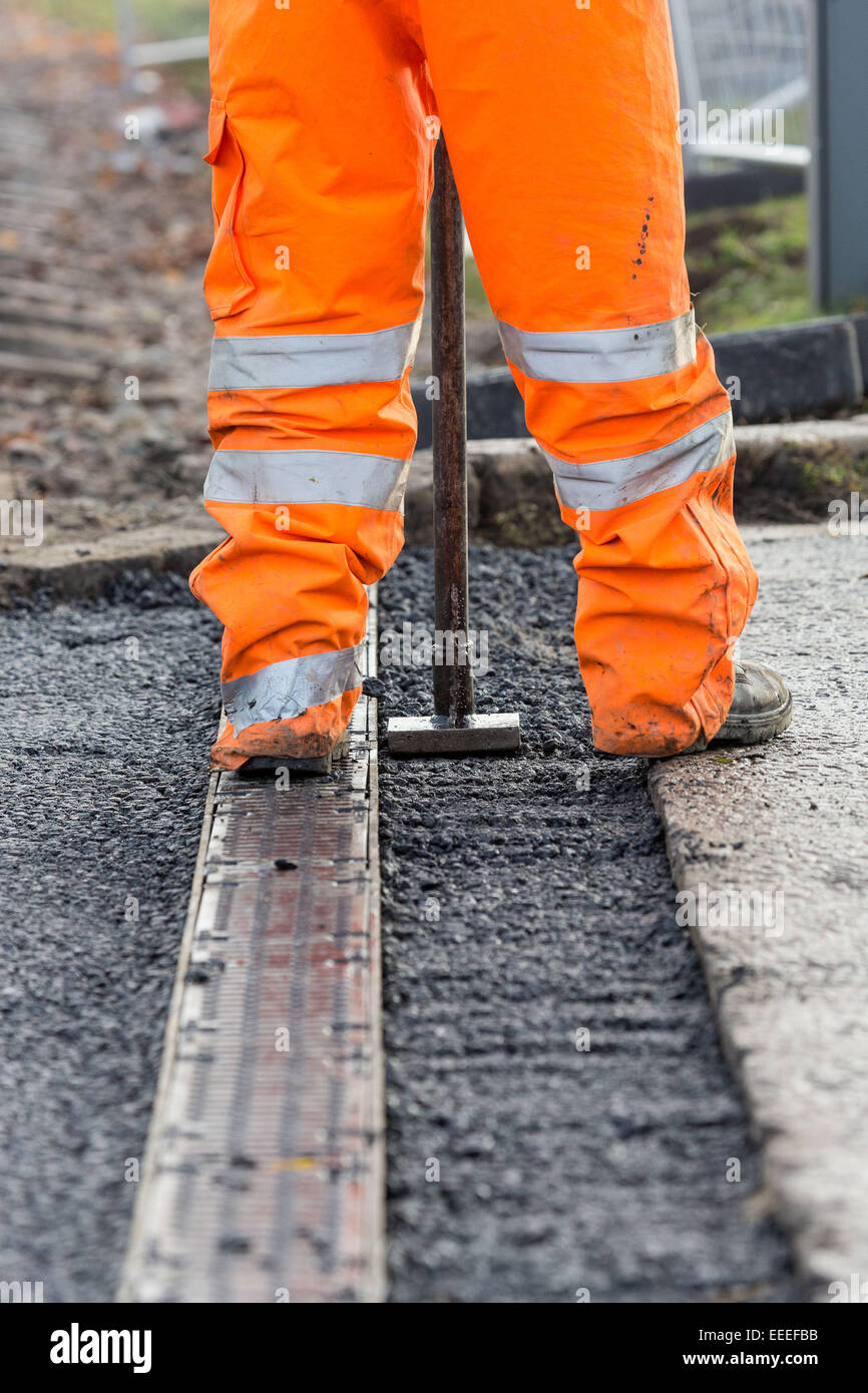Levelling tarmac at a tram worksite - Stock Image
