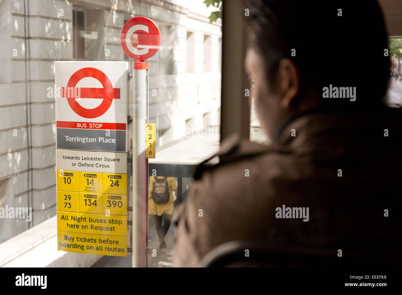 Passengers can easily read bus stop flags from the upper deck - Stock Image