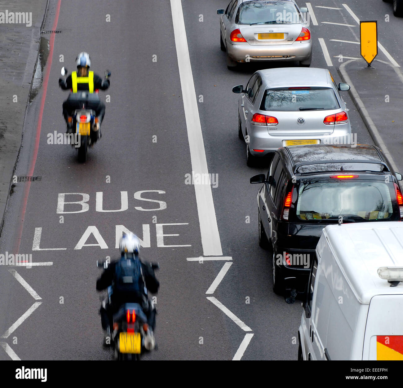 Cars stationary whilst motorbikes drive pass on the bus lane - Stock Image