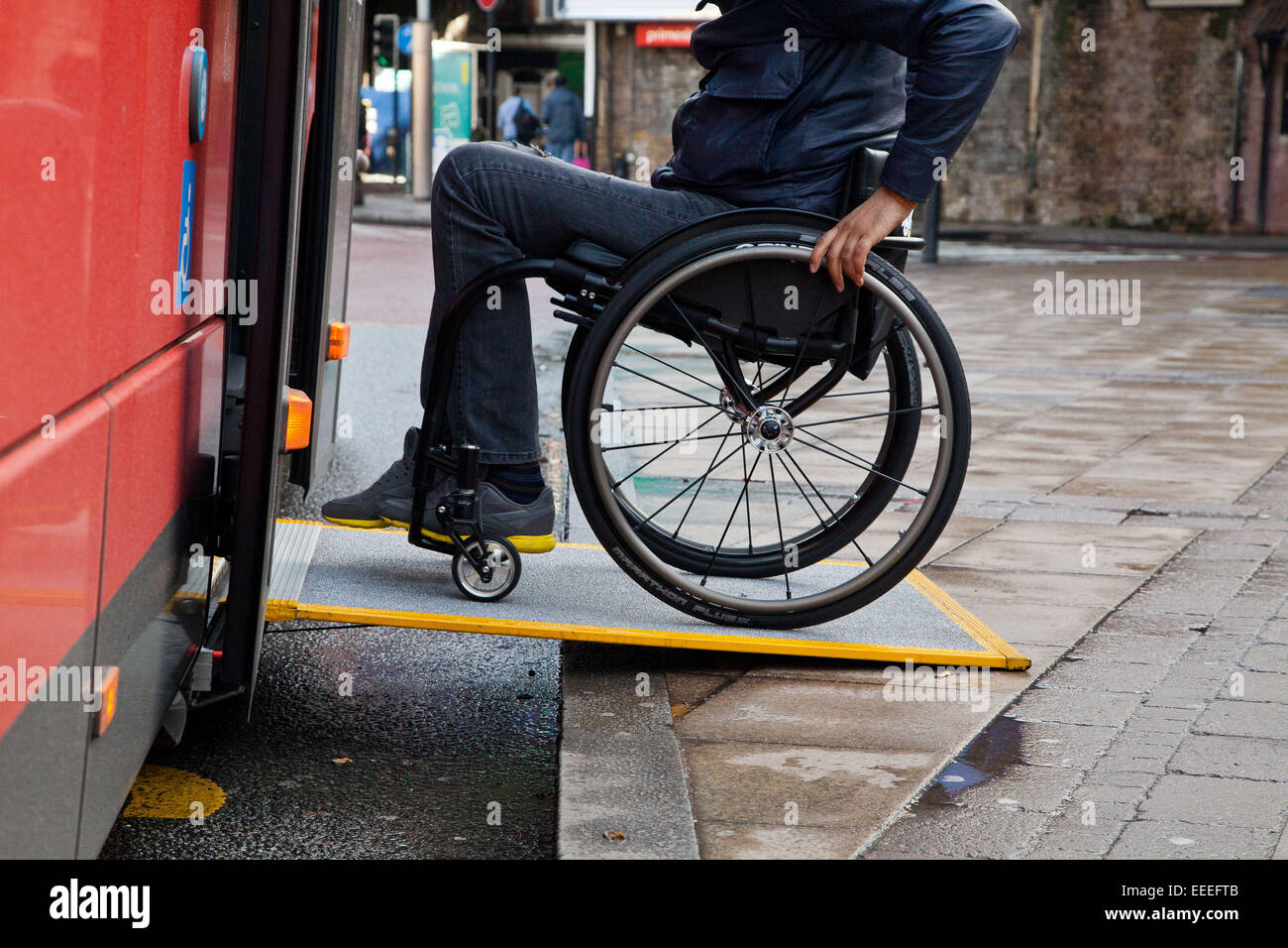 Wheelchair user boarding a London bus - Stock Image
