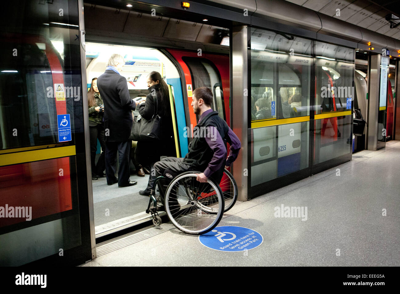 Wheelchair user boarding a London Underground train - Stock Image