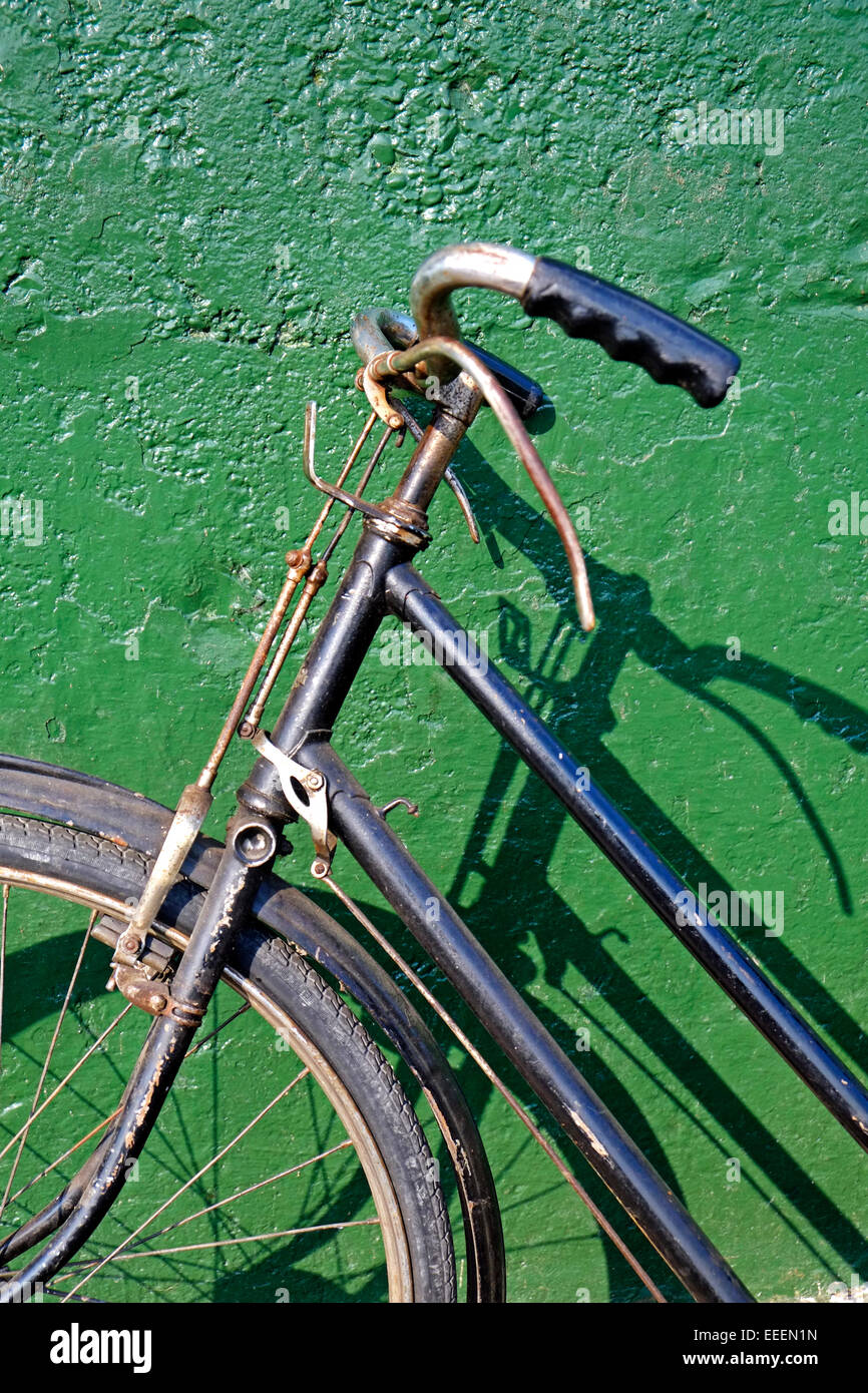 Vintage Bicycle Front end handlebars and green wall - Stock Image