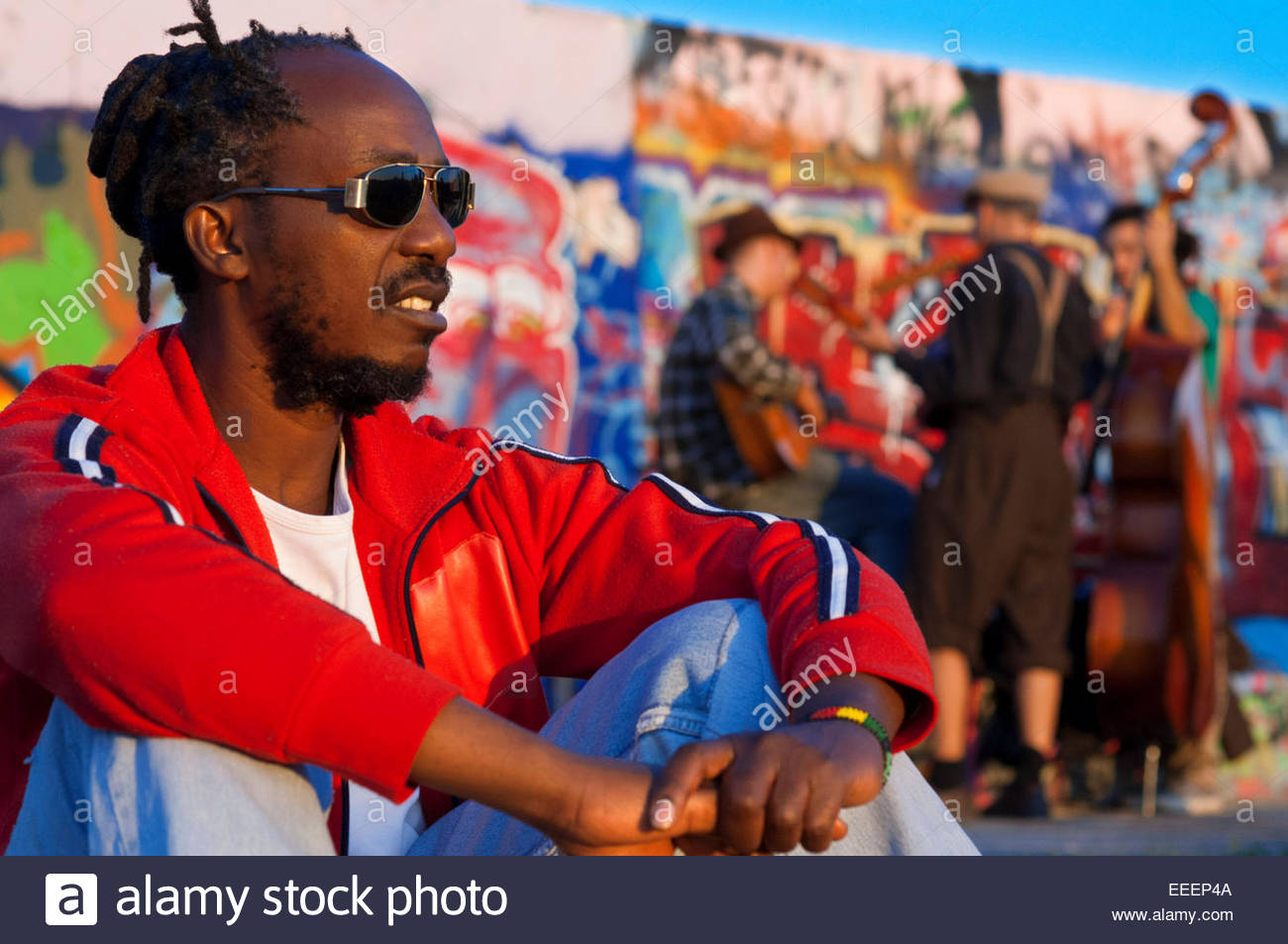 Buskers by the Wall in Mauerpark Berlin in evening light Germany. Mauerpark is a public linear park in Berlin's - Stock Image