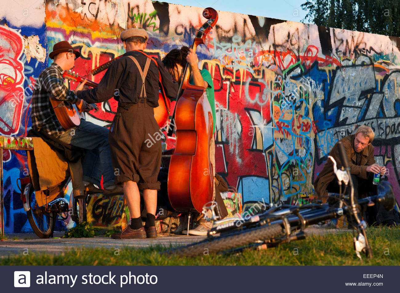 Musicians. Buskers by the Wall in Mauerpark Berlin in evening light Germany. Mauerpark is a public linear park in - Stock Image