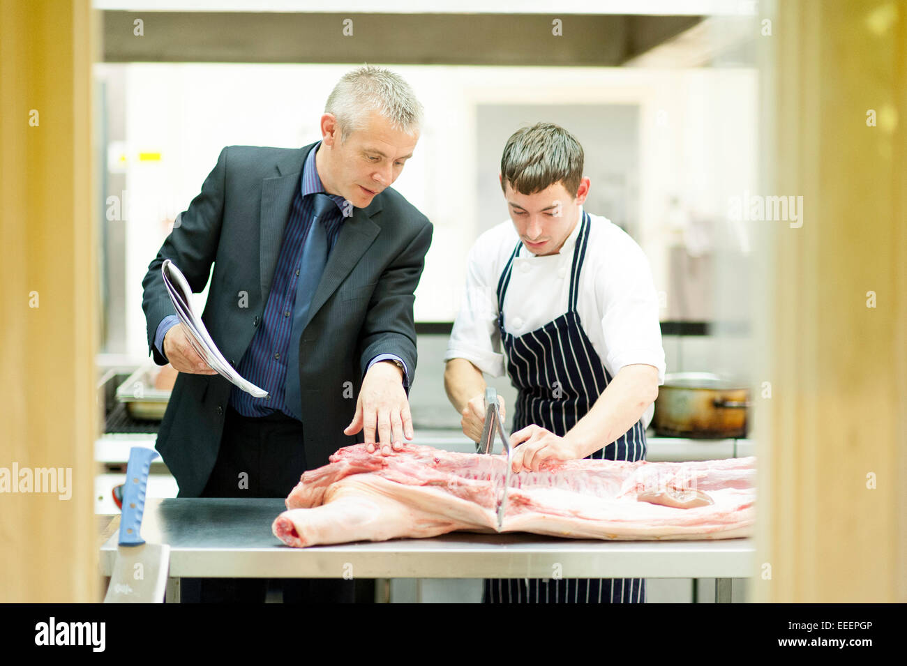 A manager teaching a trainee butcher how to cut meat - Stock Image
