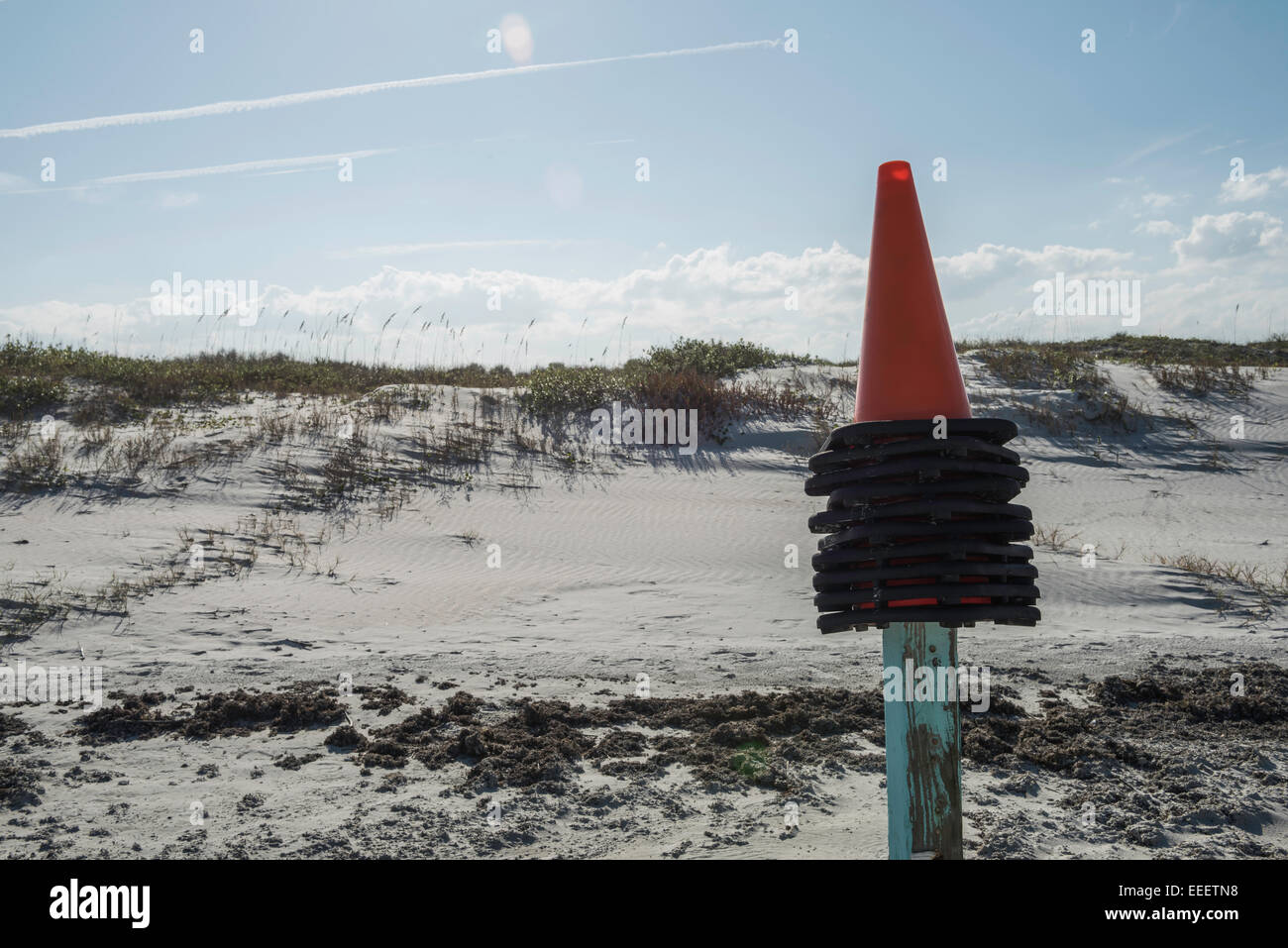 Stacked orange and black traffic cones placed atop a wooden post with weathered light blue paint in front of Daytona - Stock Image