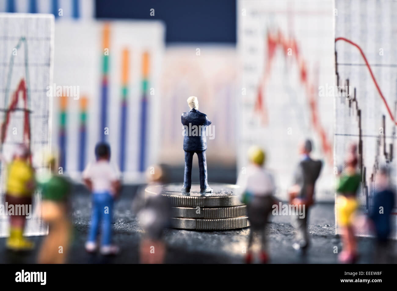 Banker looks on boards with various charts, symbolizing the ups and downs in the markets. He stands on a base of Stock Photo