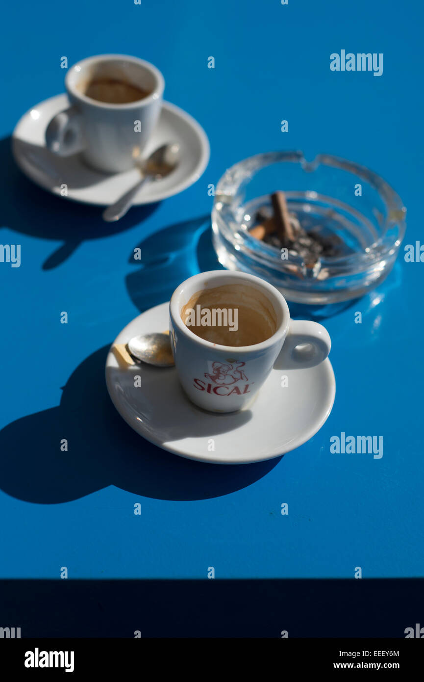 two empty espresso coffee cups and an ashtray on a blue table - Stock Image