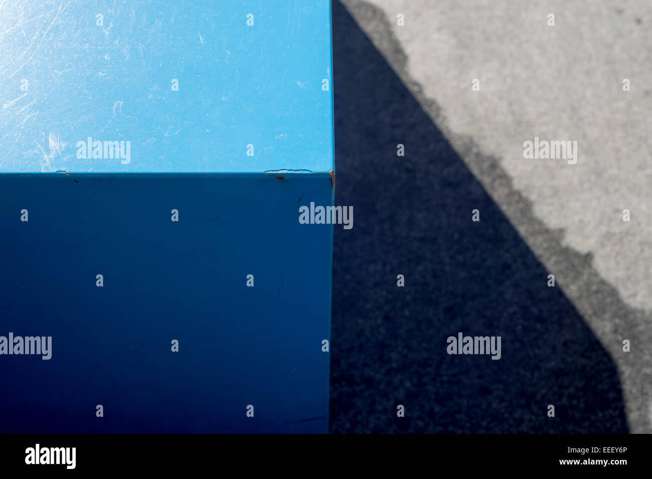 abstract view of the corner of a blue table on a concrete floor - Stock Image