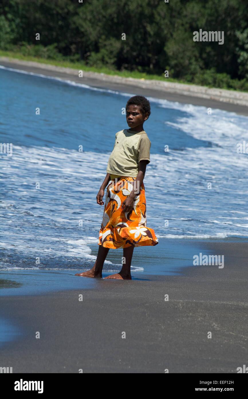 Melanesia, Vanuatu, Tanna Island. Young pregnant village girl standing on the beach. - Stock Image