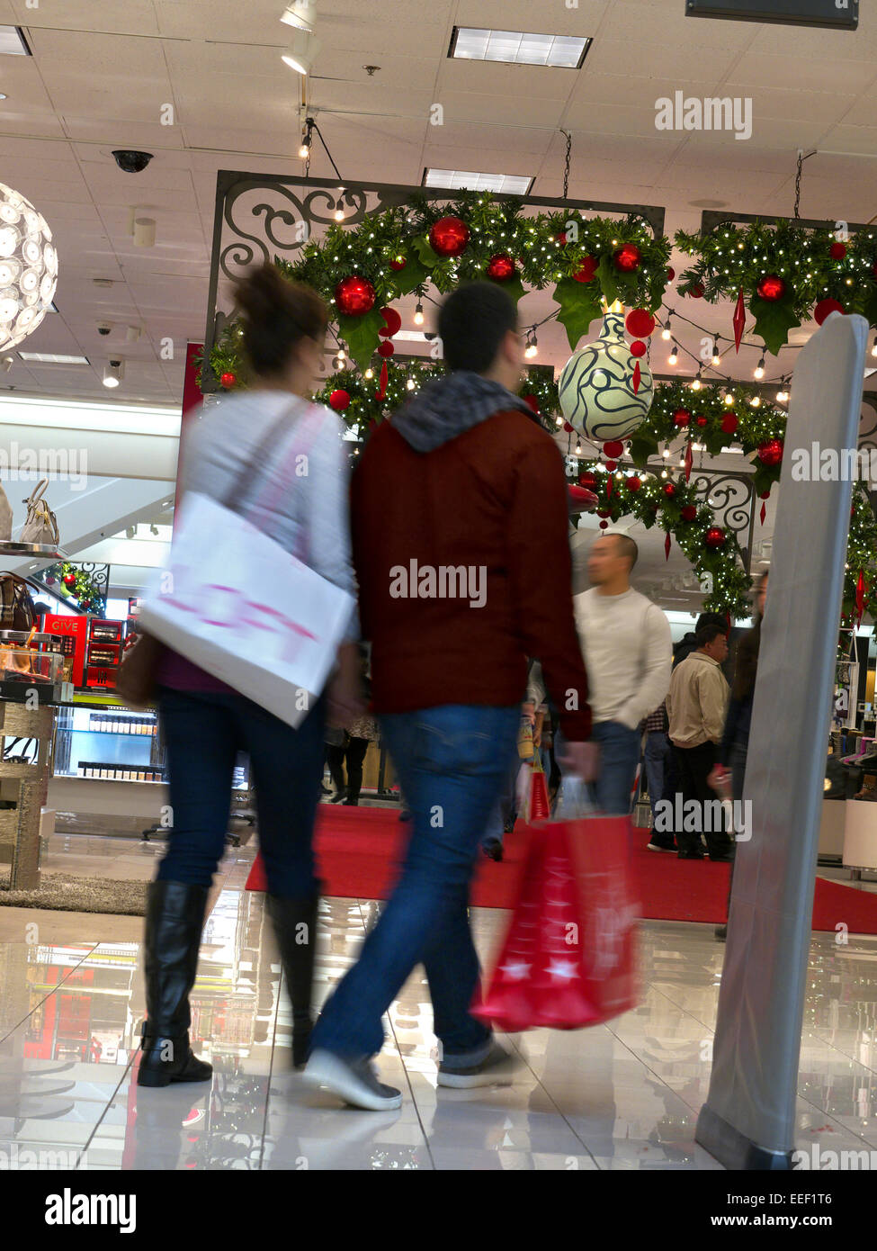 Christmas shoppers in shopping mall with electronic security tag detector at store entrance in foreground - Stock Image