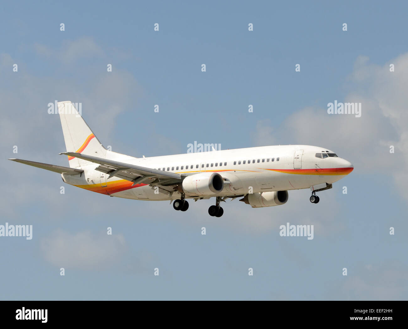 Passenger jet airplane landing with gear down Boeing 737 - Stock Image