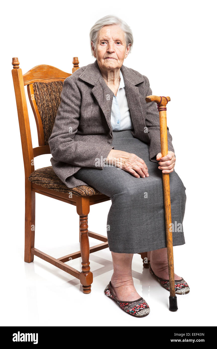 Senior woman with walking stick sitting on chair over white background - Stock Image