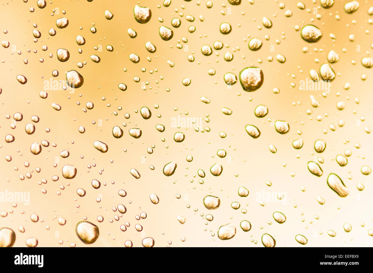 Water droplets on clear glass reflect ambient light producing interesting patterns. - Stock Image