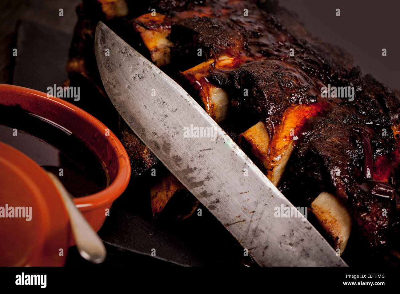 Beef ribs cooked on the BBQ and served with sweetcorn and a red wine souse. - Stock Image