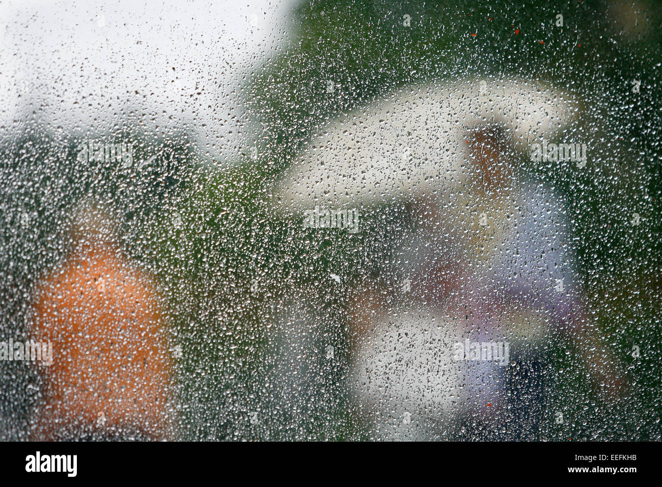 Rain on a window looking out to people in a street scene - Stock Image