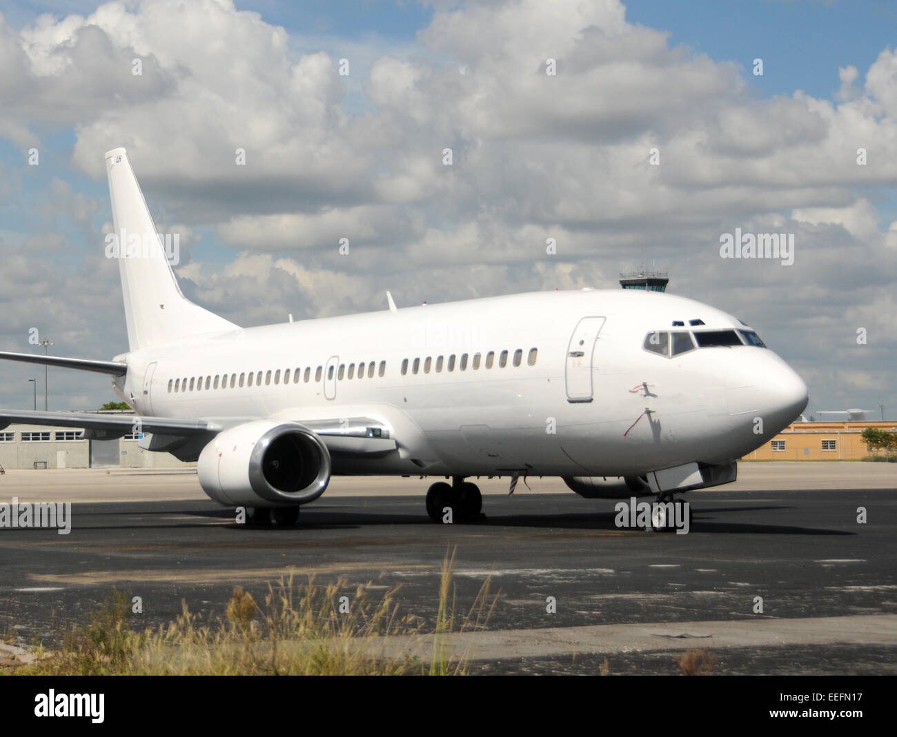 Modern passenger jet airplane in unmarked white paint Boeing 737 - Stock Image