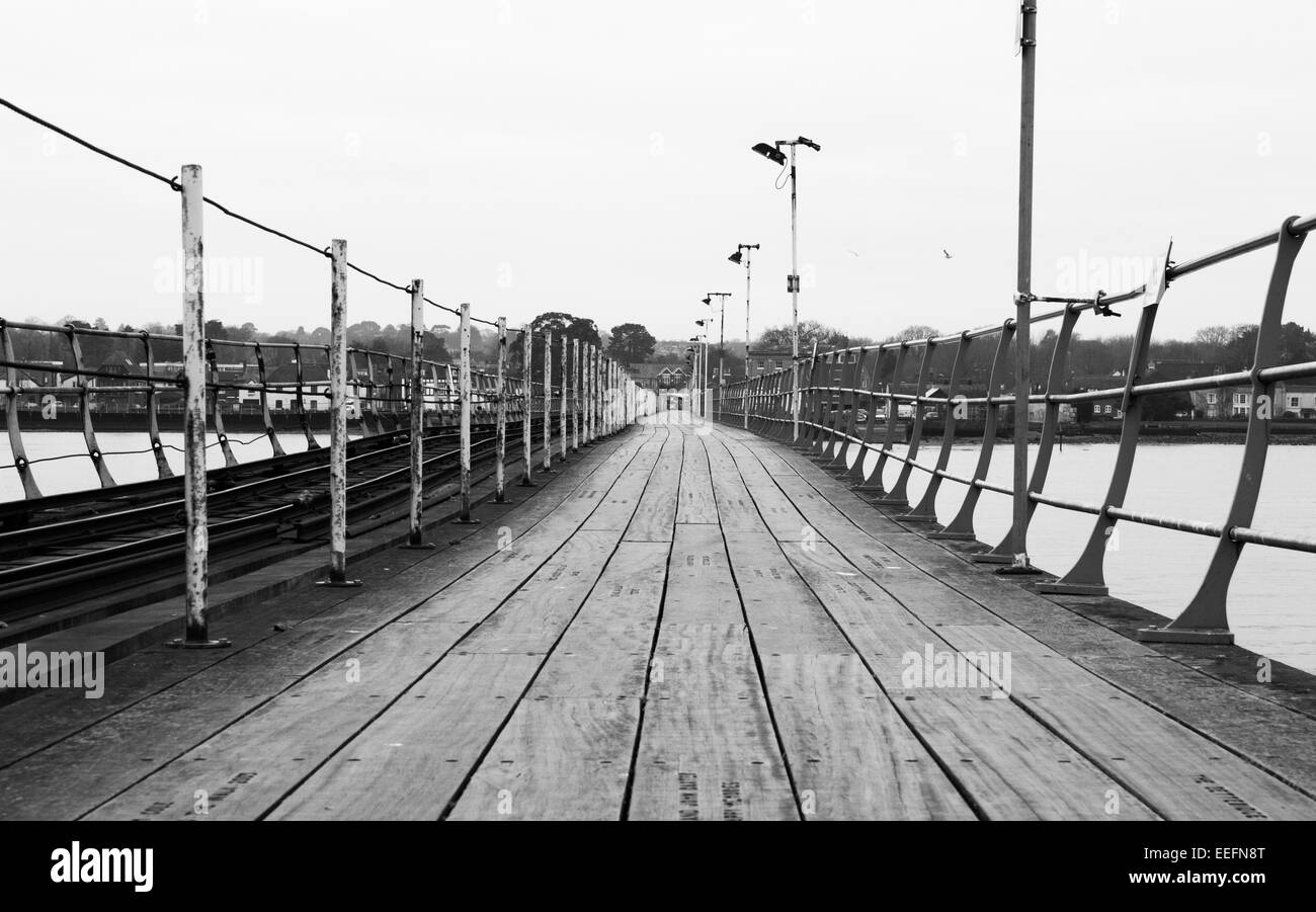 Looking down the wooden planks of Hythe Pier in Hythe, Hampshire. - Stock Image