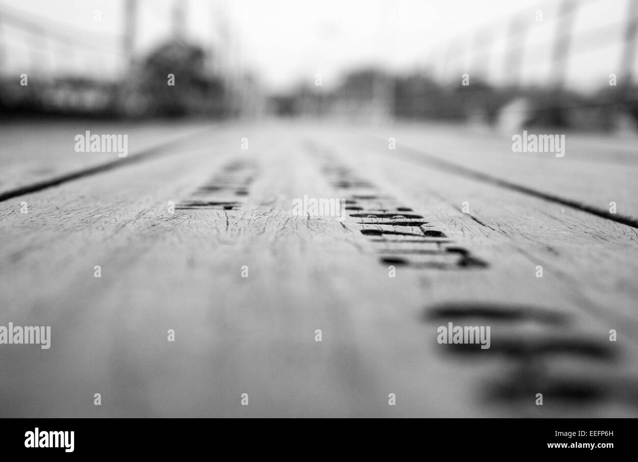 Shallow depth of field on the planks of Hythe Pier and the written memorials along the pier. - Stock Image