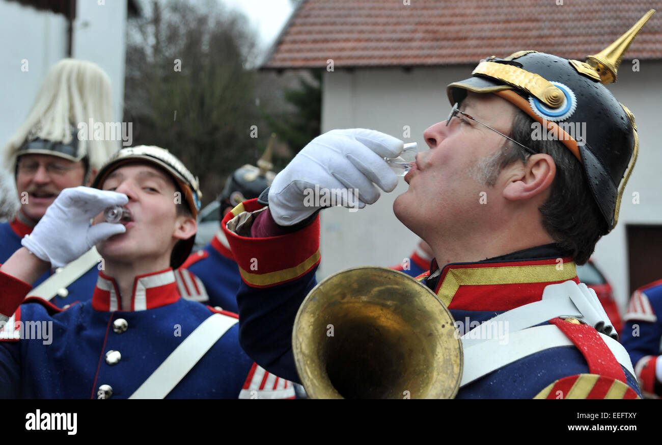 Gammelsdorf, Germany. 17th Jan, 2015. Two musicians in traditional costume warm up with schnaps in Gammelsdorf, - Stock Image
