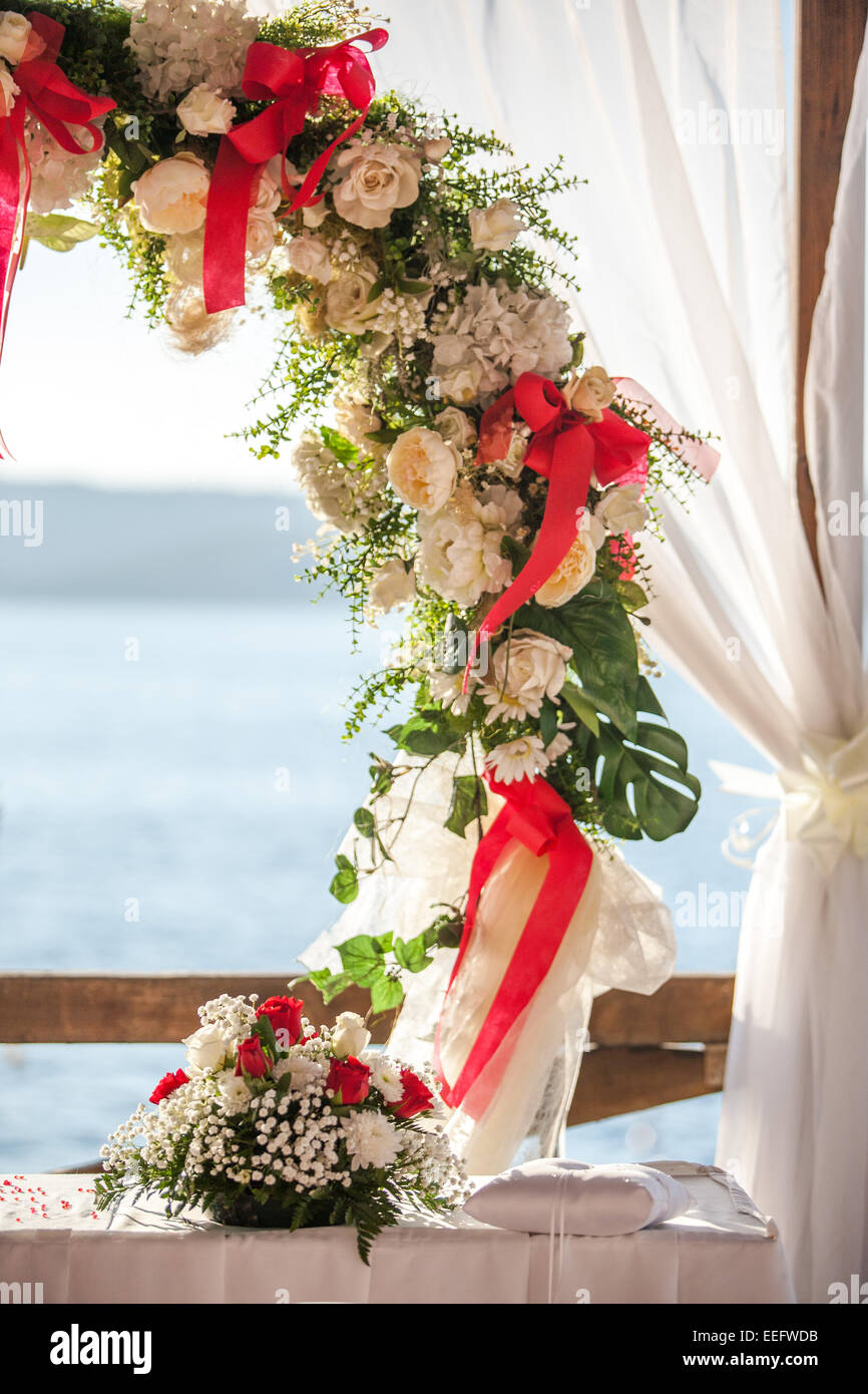 Wedding venue ceremony setup - red material / flowers - Stock Image