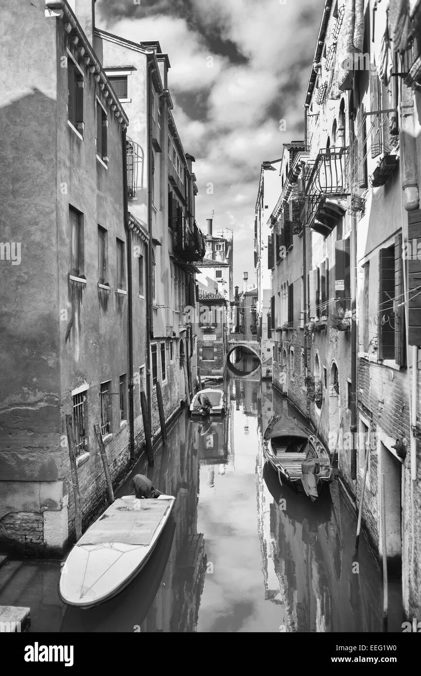 A view of empty boats parked next to buildings in a water canal in Venice, Italy. - Stock Image