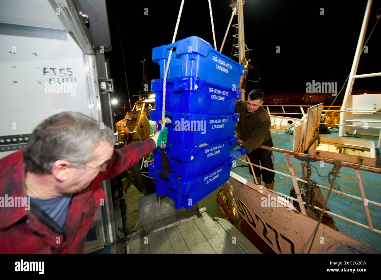2 fishermen offloading a catch from a UK trawler - Stock Image