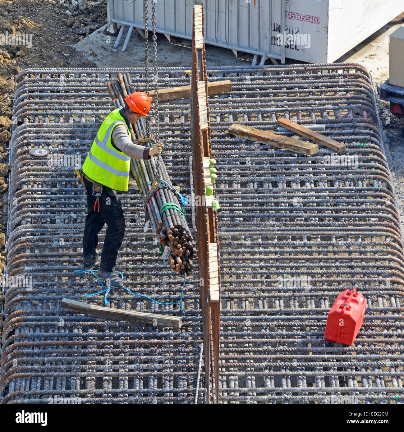 Steelfixer guiding a crane lowering bundle of reinforcing rods onto steel foundation frame construction site London - Stock Image