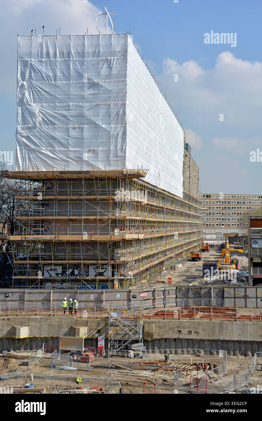Social housing estate cocooned in plastic sheeting &scaffolding for demolition new building work started on - Stock Image