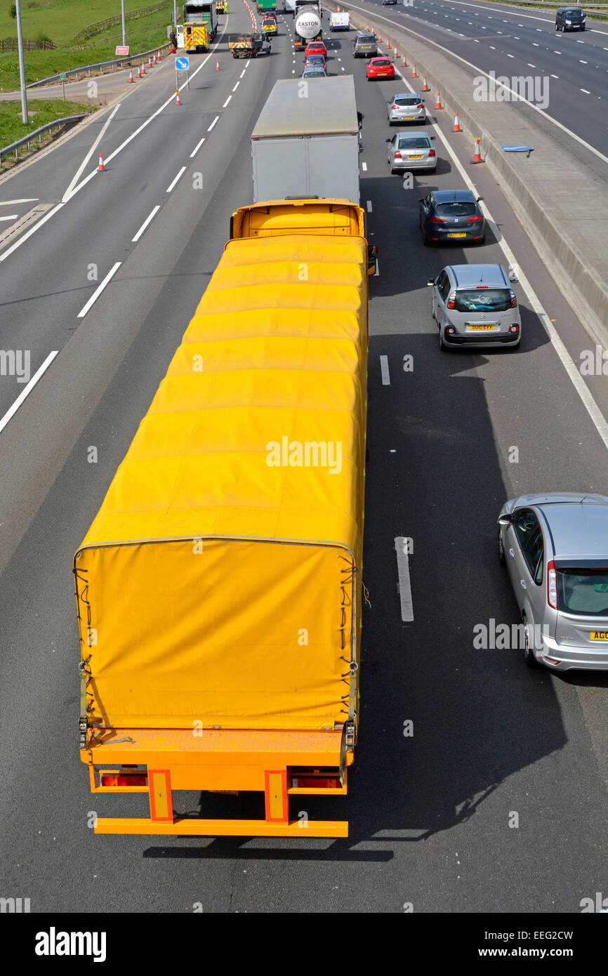 Slow moving motorway traffic using two lanes because of obstructions ahead (trailer number plate digitally removed) - Stock Image