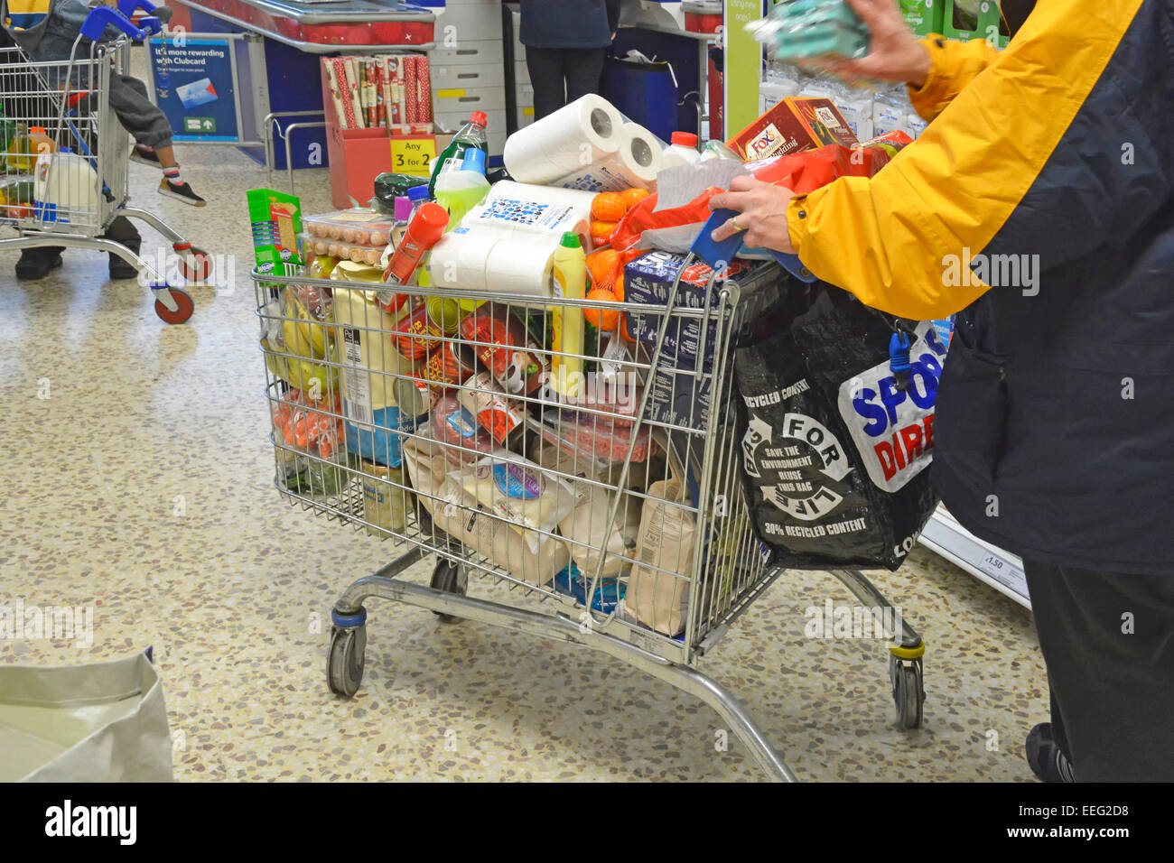 Shopper with full overflowing supermarket shopping trolley a week before Christmas Day London England UK - Stock Image