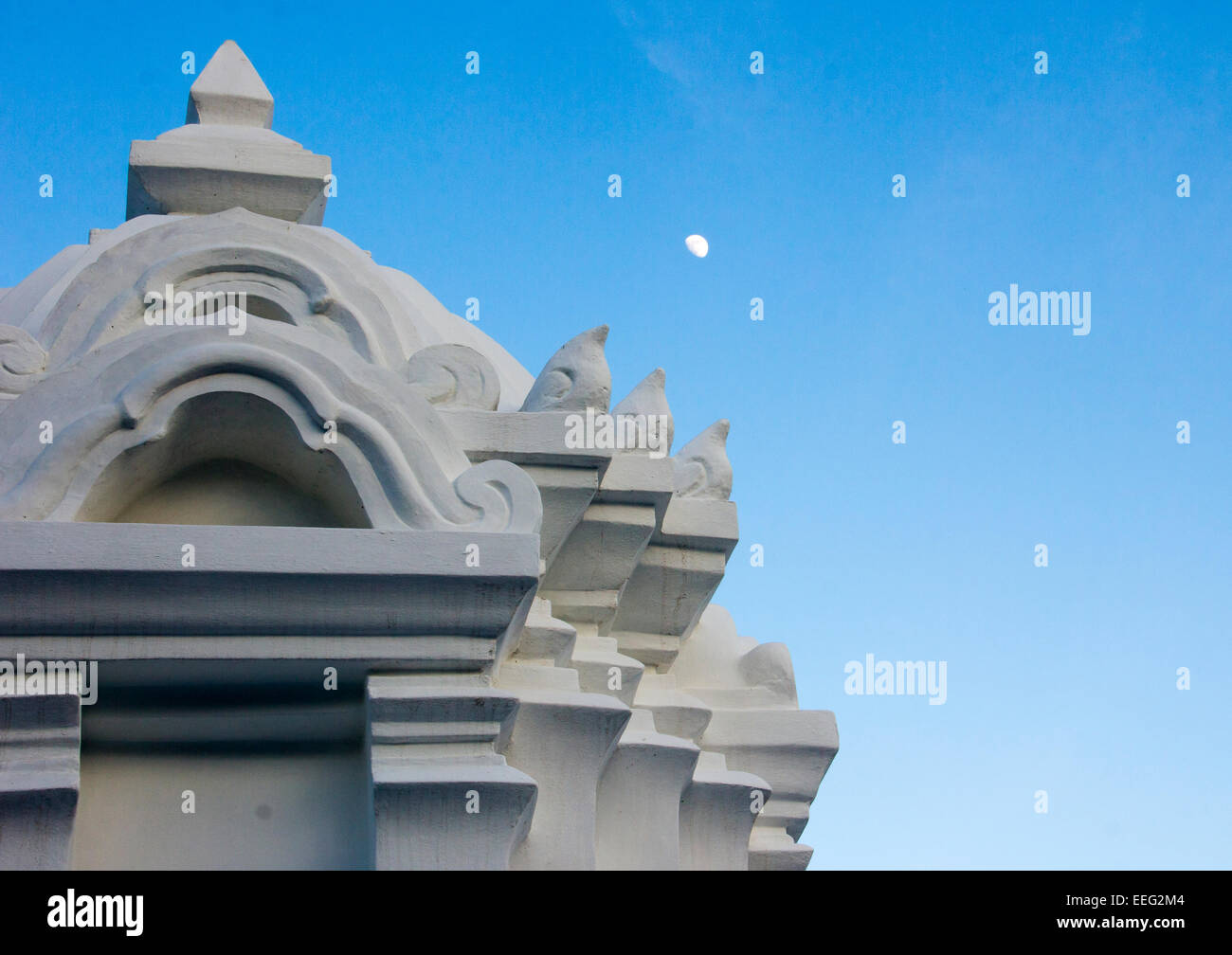 Moon rising over temple in Thailand. - Stock Image