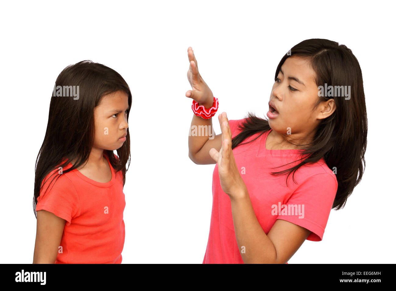 Teenager shocked by the angry reaction of her little sister - Stock Image
