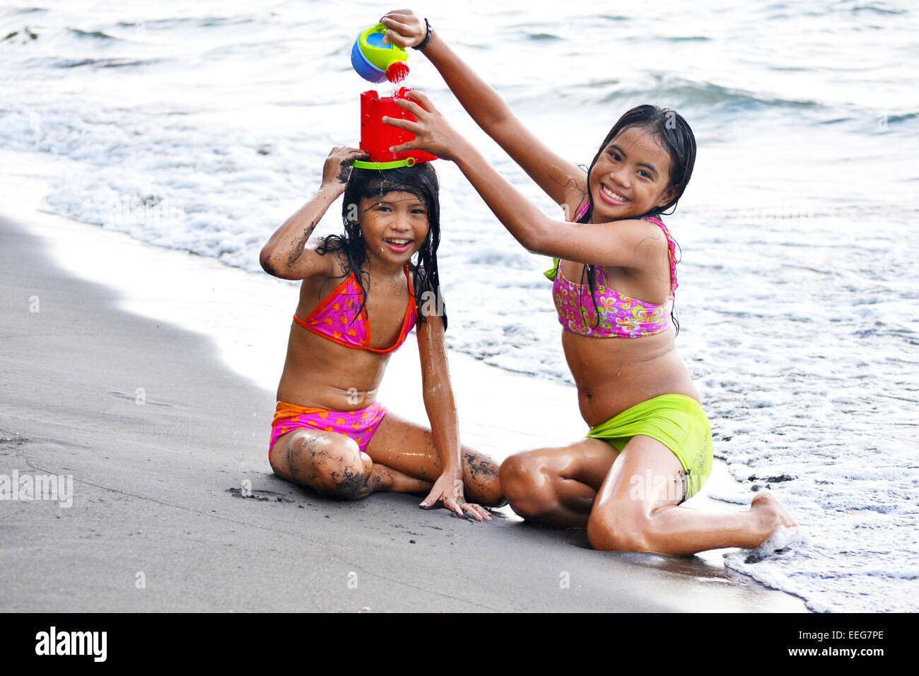 Two little sisters playing on the beach with beach toys! - Stock Image