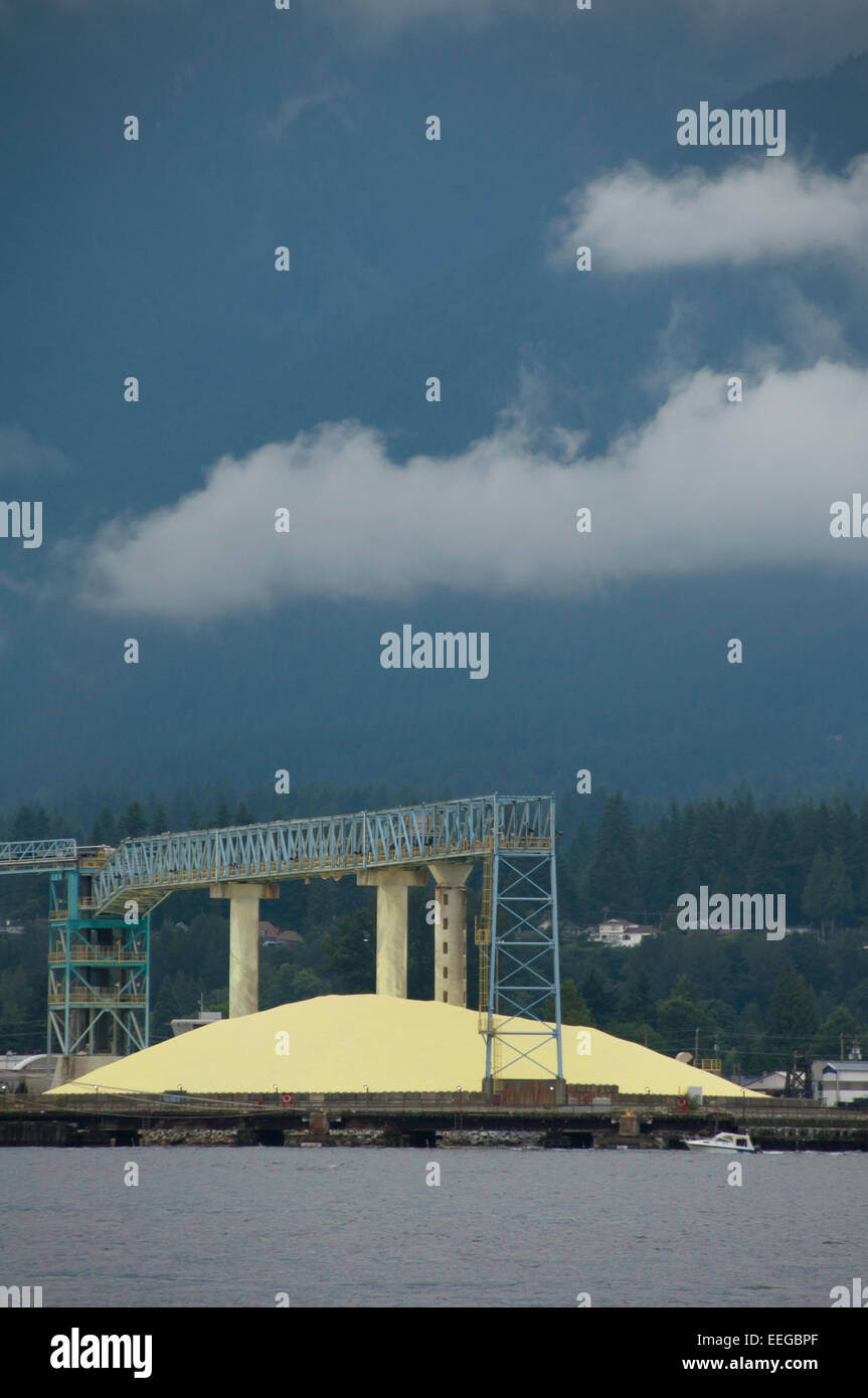 Giant pile of sulphur at Vancouver Wharves bulk marine terminal ready for shipment around the world for use in fertilizers - Stock Image