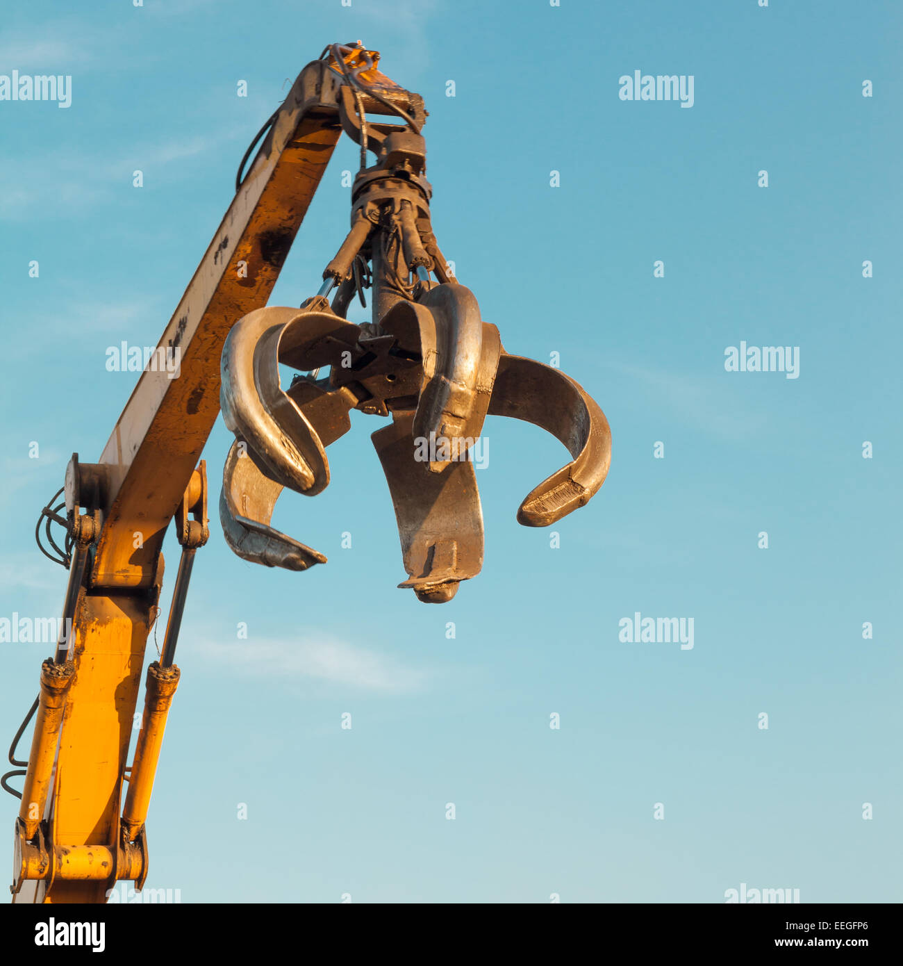 crane arm with open claw on clear blue sky - Stock Image