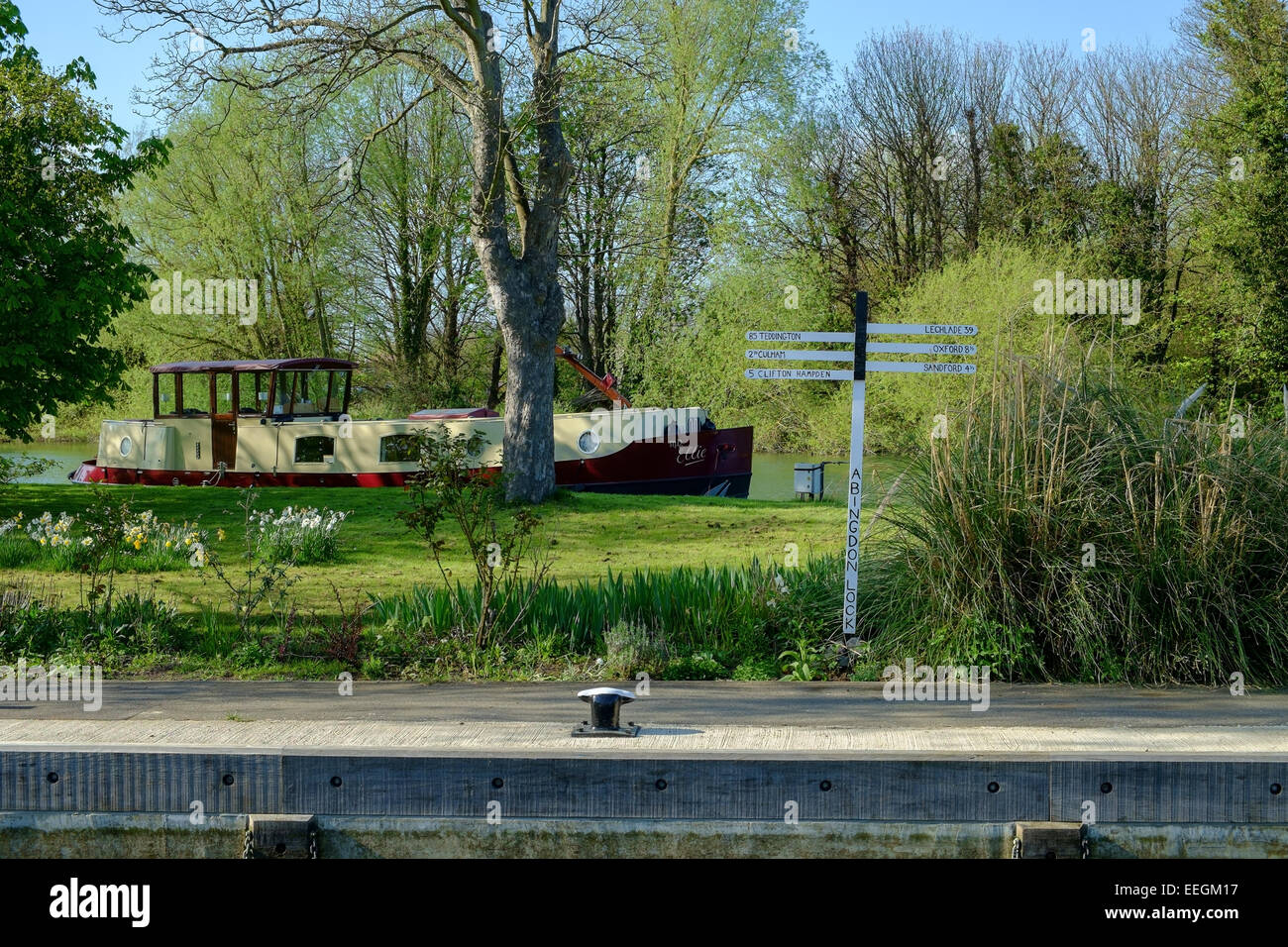 A signpost and boat by the canal and River Thames, at Abingdon, UK. Stock Photo