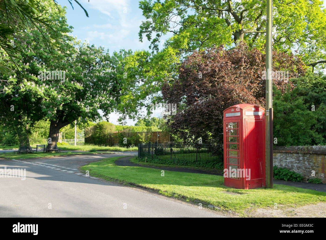 A traditional red telephone box in an English village. - Stock Image