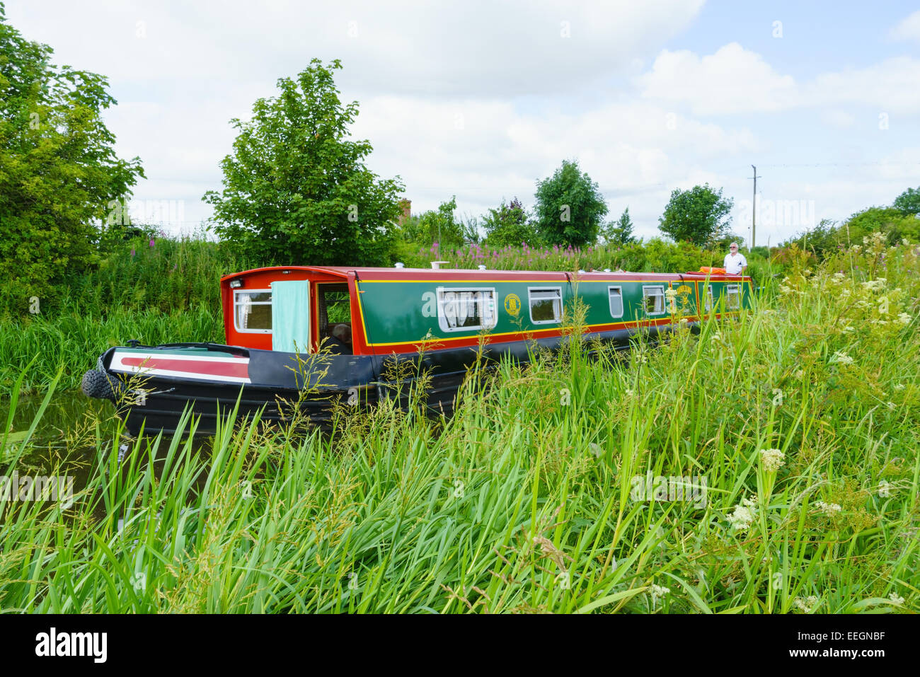A narrowboat on the Union Canal travelling through grassy fields, near Edinburgh. - Stock Image