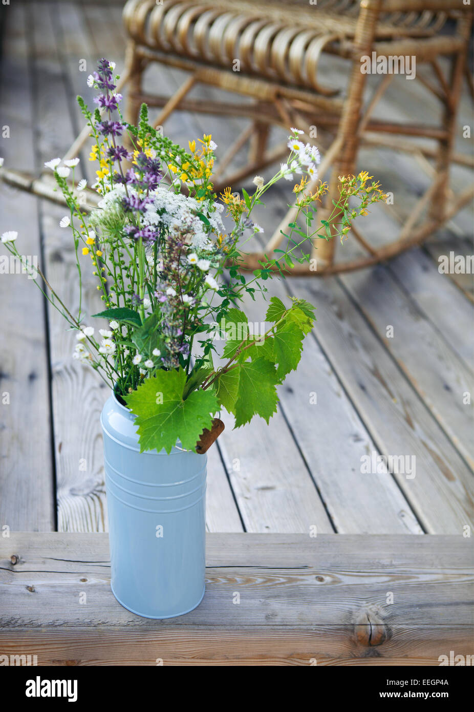 Bright yellow and blue bucket with flowers on porch near the Adirondack rocking chair - Stock Image