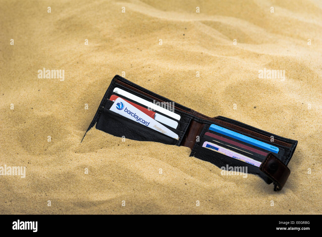 Wallet dropped and half buried on a sandy beach. - Stock Image