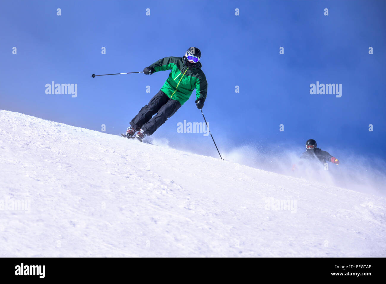 Two Skiers skiing downhill in high mountains and sunny day - Stock Image