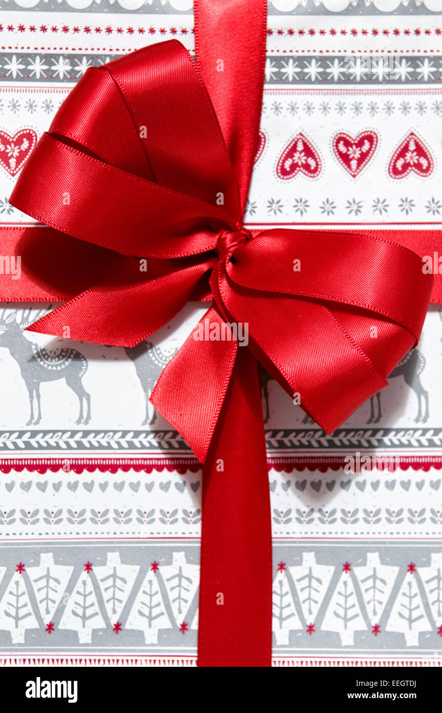 Close up of Christmas present with hand made red bow - Stock Image