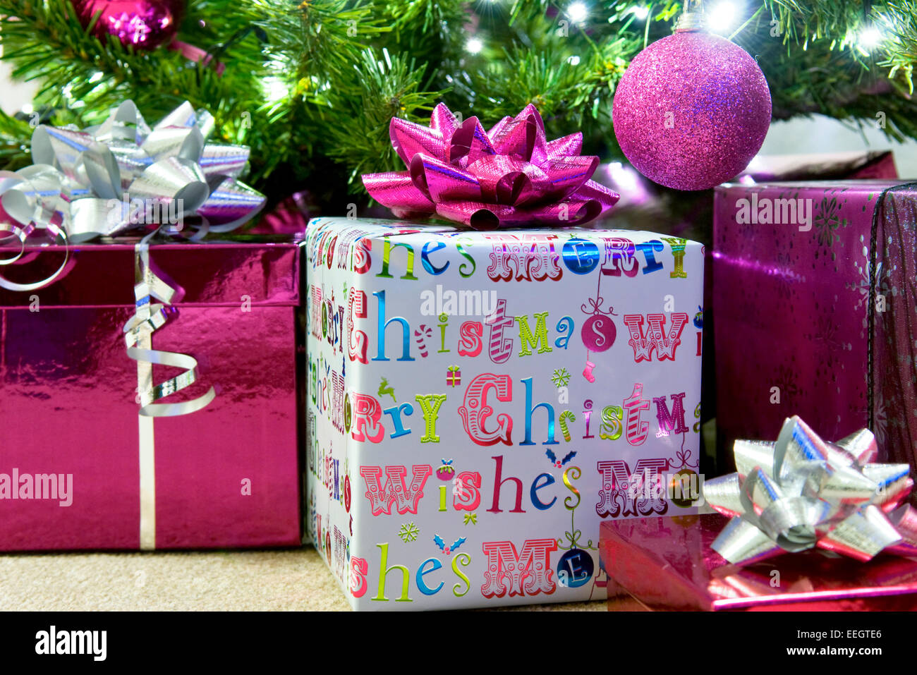 Close up of prettily wrapped Chistmas presents under tree in modern theme and colours - Stock Image