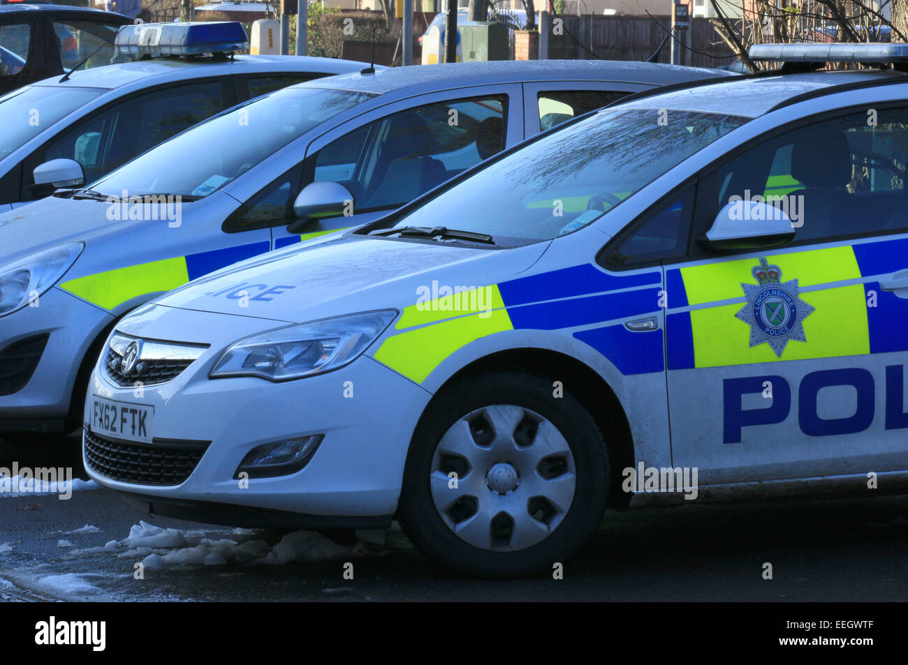 Police cars in the snow Vauxhall (MG) and Fords, outside small local police station, an old semi detached house, - Stock Image