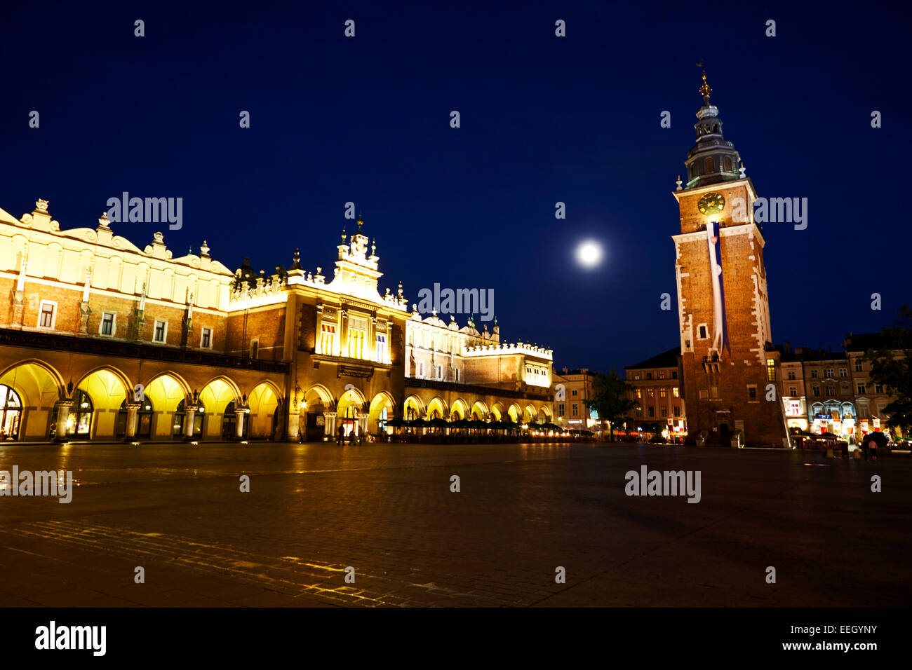 the moon rising over Rynek Glowny main town square in the stare miastro with krakow at night cloth hall town hall - Stock Image