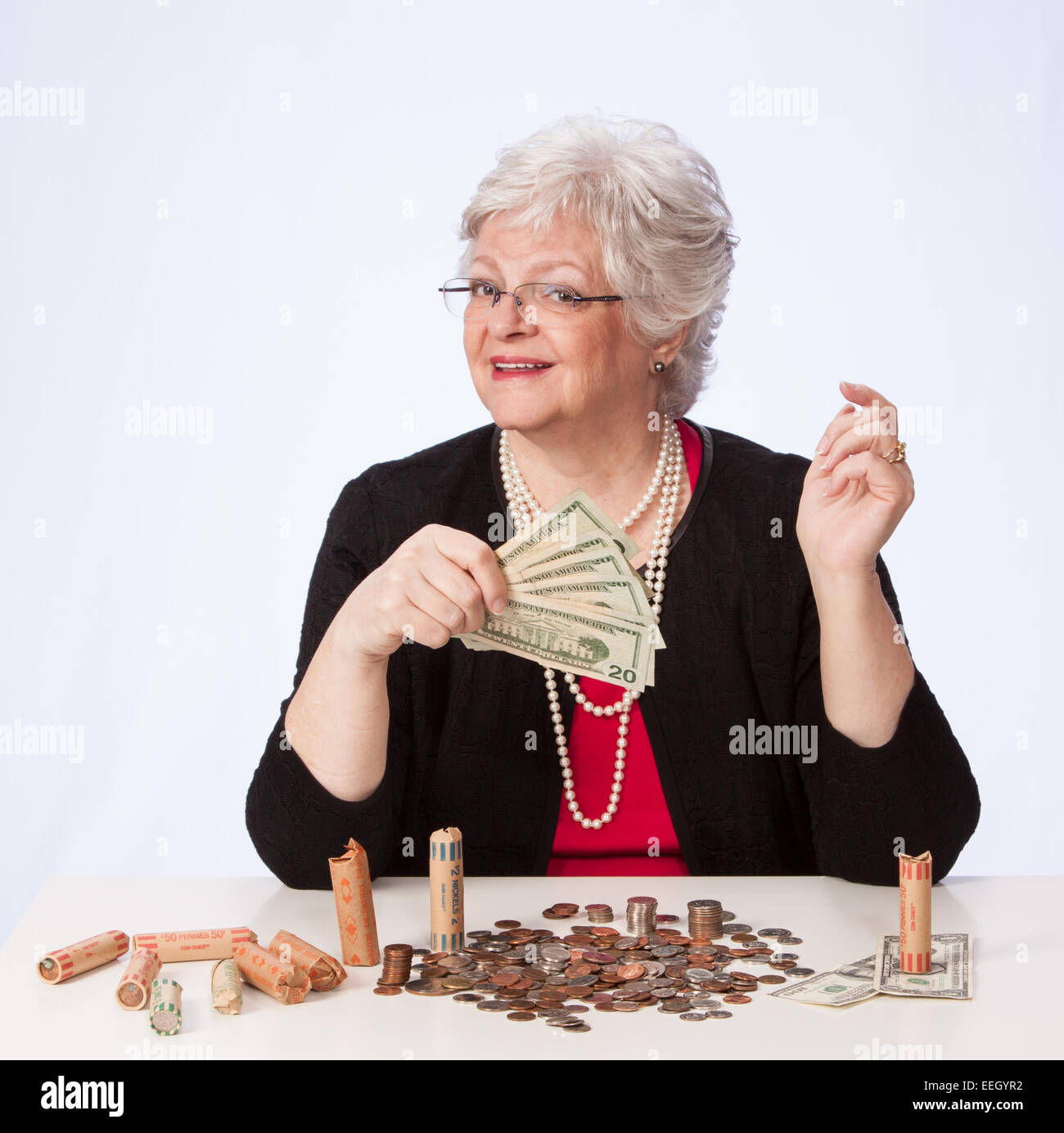 Mature Woman in Pearls fans $20 dollar bills ready for retirement - Stock Image