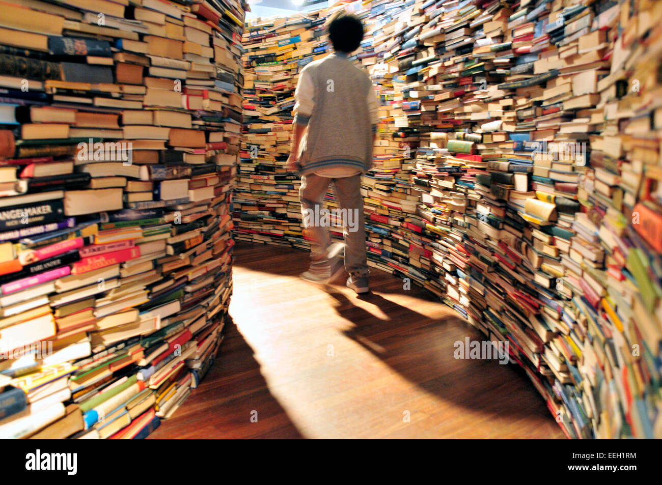 a-young-boy-walks-between-piles-of-books