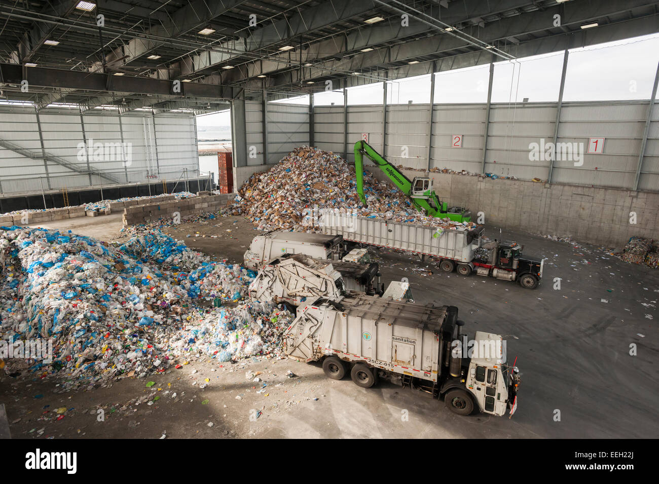 Garbage trucks dump trash in the tipping area from the city's curbside recycling program at the Sims Municipal - Stock Image