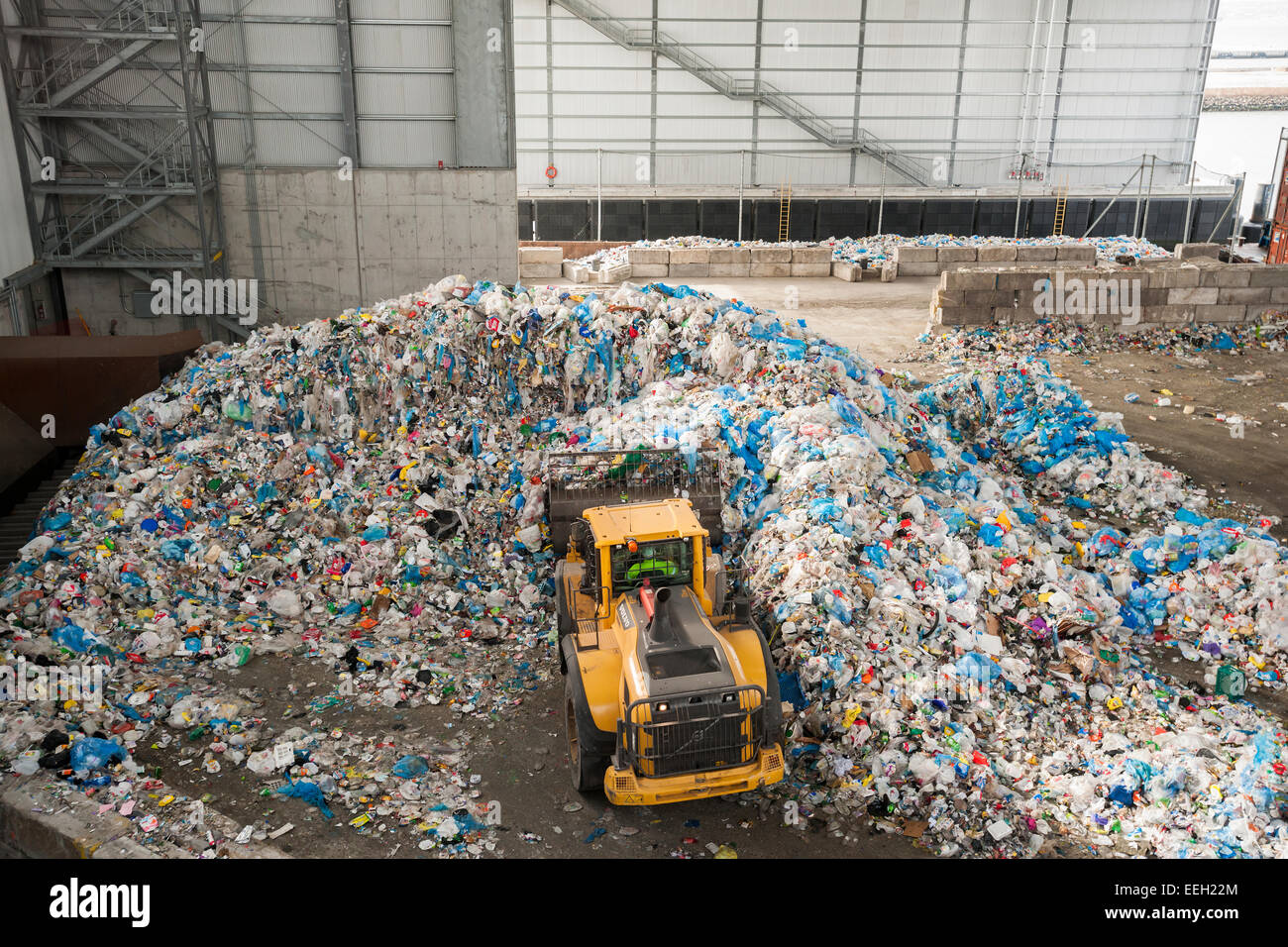 A front loader moves mountains of trash in the tipping area from the city's curbside recycling program at the - Stock Image